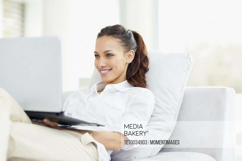 Woman relaxing on couch with laptop
