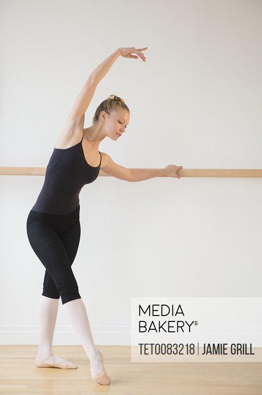 Portrait of teenage 16-17 ballet dancer standing in ballet position at barre