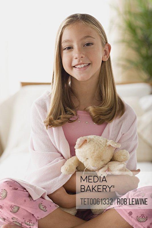 Smiling girl (12-13) holding teddy bear