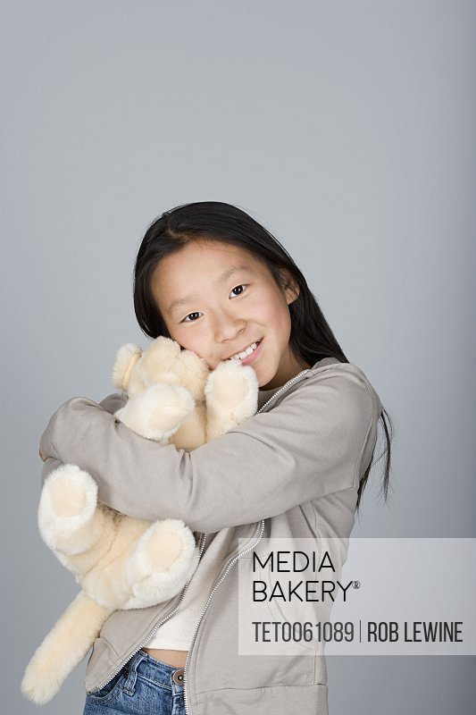 Studio portrait of teenage Chinese girl (16-17) hugging teddy bear
