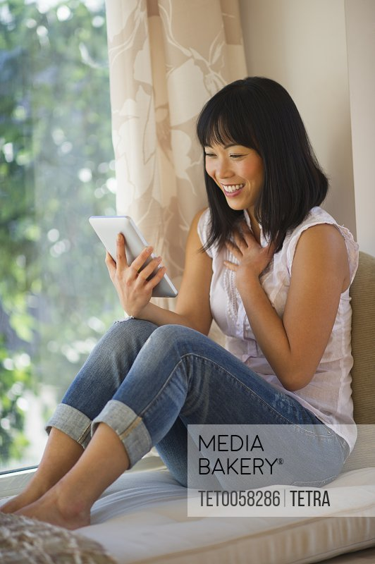Smiling mid adult woman using digital tablet