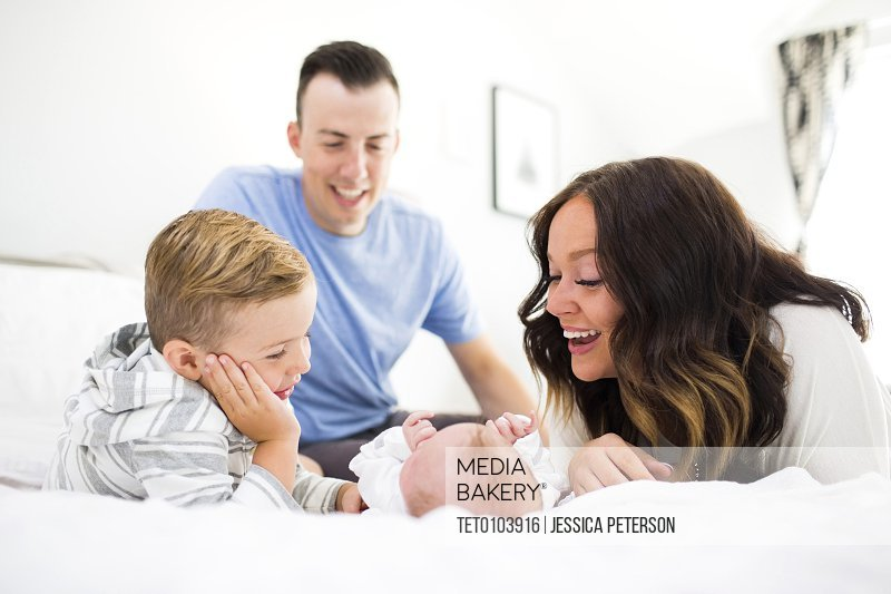 Photo by Tetra Images - Parents son (4-5) and daughter ( 1 month) in bedroom
