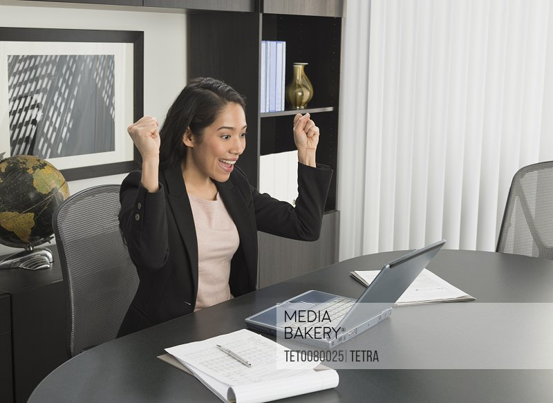 Businesswoman expressing happiness at desk