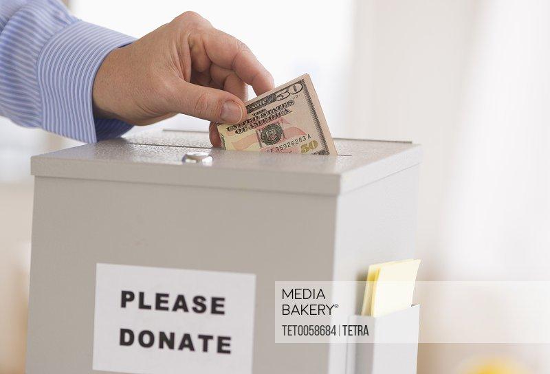 Man's hand putting dollars into donation box