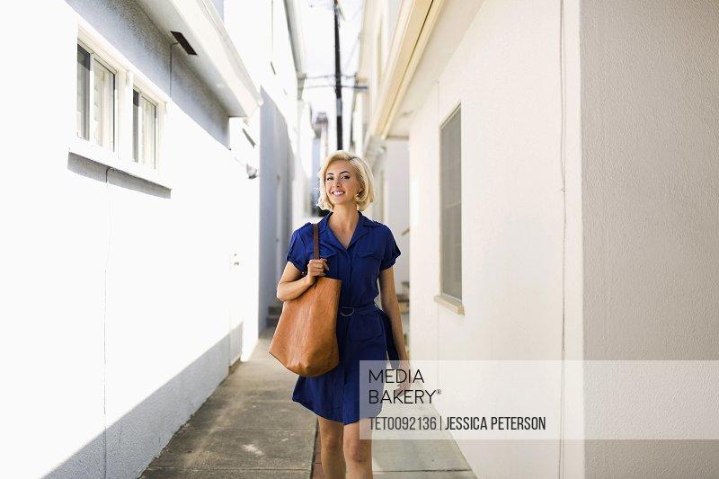 Front view of women in blue dress walking between white buildings