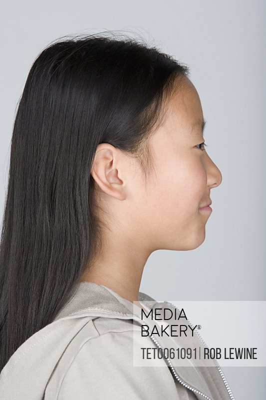 Studio portrait of happy Chinese teenage girl (16-17)