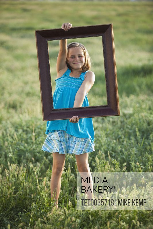 Young girl holding picture frame