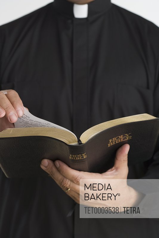Close up of bible in priest's hands