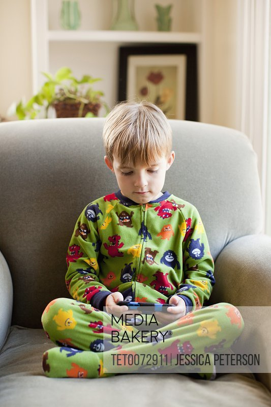 Boy in his pijamas sitting on armchair and playing video game