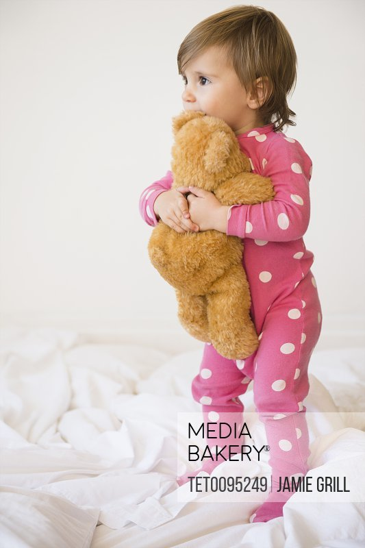 Girl 2-3 embracing teddy bear on bed