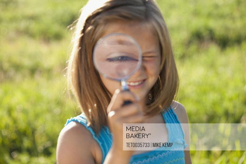 Young girl holding a magnifying glass