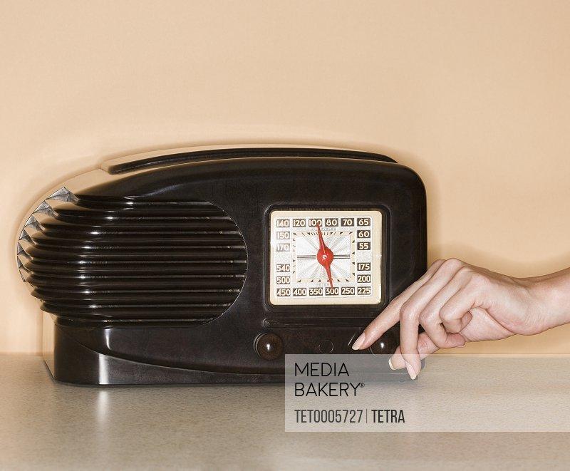 Woman turning knob on old fashioned radio