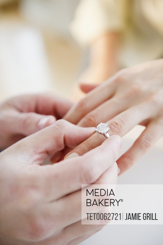 Close up of man's and woman's hands with engagement ring