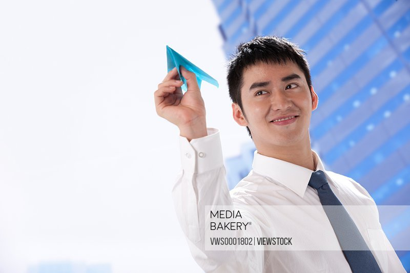 Young businessman holding paper plane