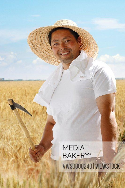 Farmer holding scythe in wheat field