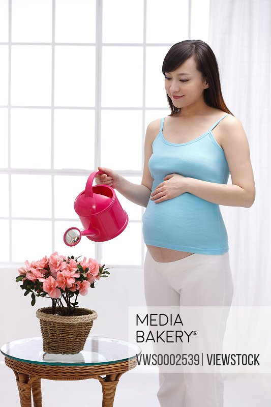 Pregnant woman watering the flowers