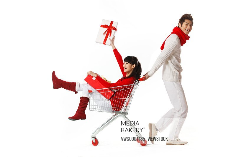 Young man pulling young woman in shopping cart