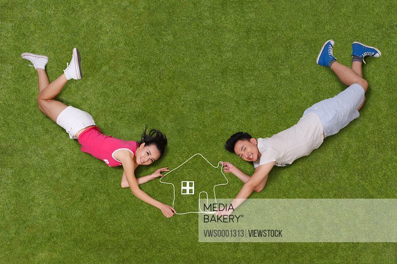 Young people lying on grass with an artificial house