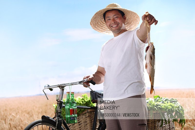 Farmer holding fish,standing by bicycle