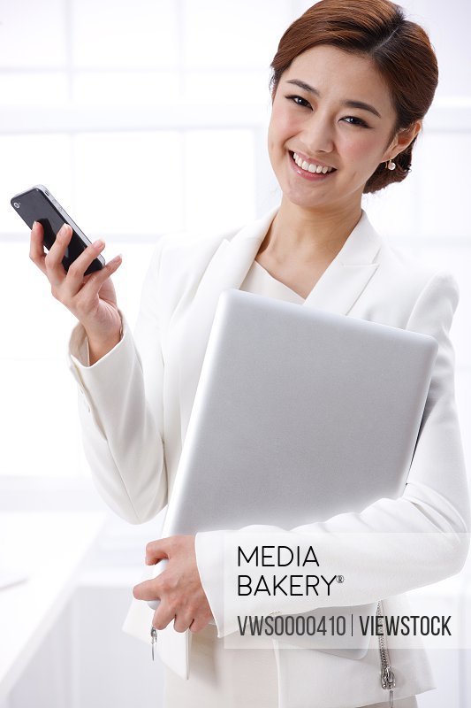 Young business lady holding cellphone and laptop