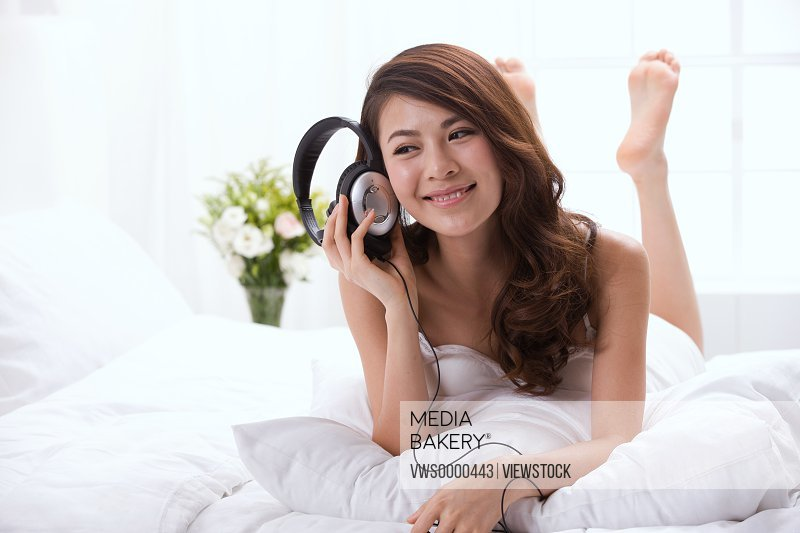 Young couple listening to music on bed
