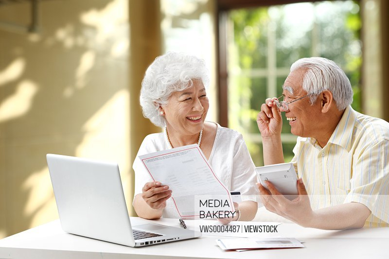 Happy elderly couple reading report