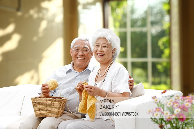 Happy elderly couple knitting