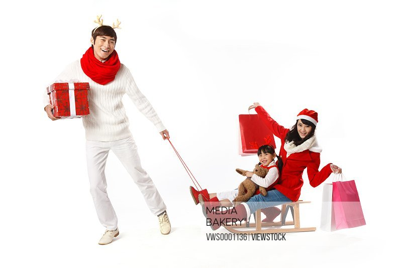 Young man pulling girl and young woman on sled