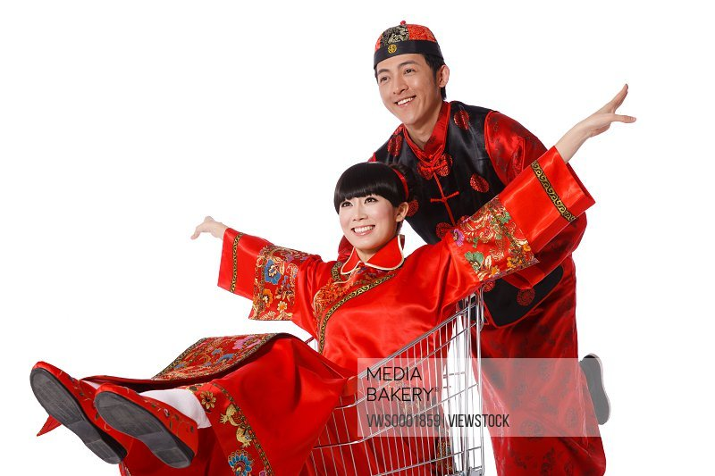Young couple dressed in traditional clothes shopping with cart