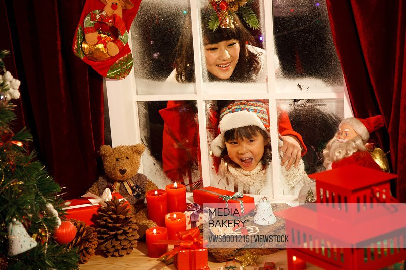 Young woman and girl looking at Christmas gift through window