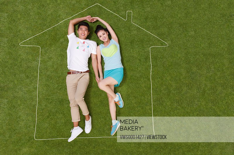 Young couple lying on grass in an artificial house