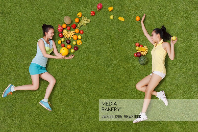 Young women lying on grass with fruits