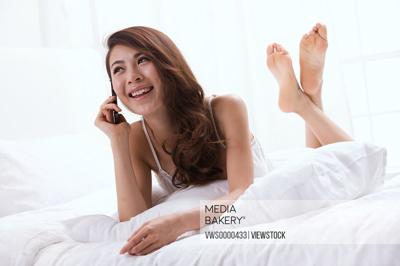 Young lady making phone call on bed
