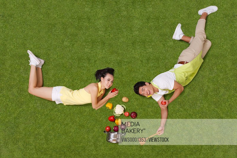 Young couple lying on grass with vegetables