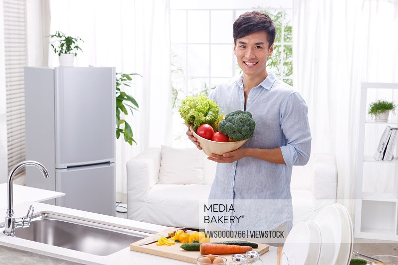 Young man holding vegetables in kitchen
