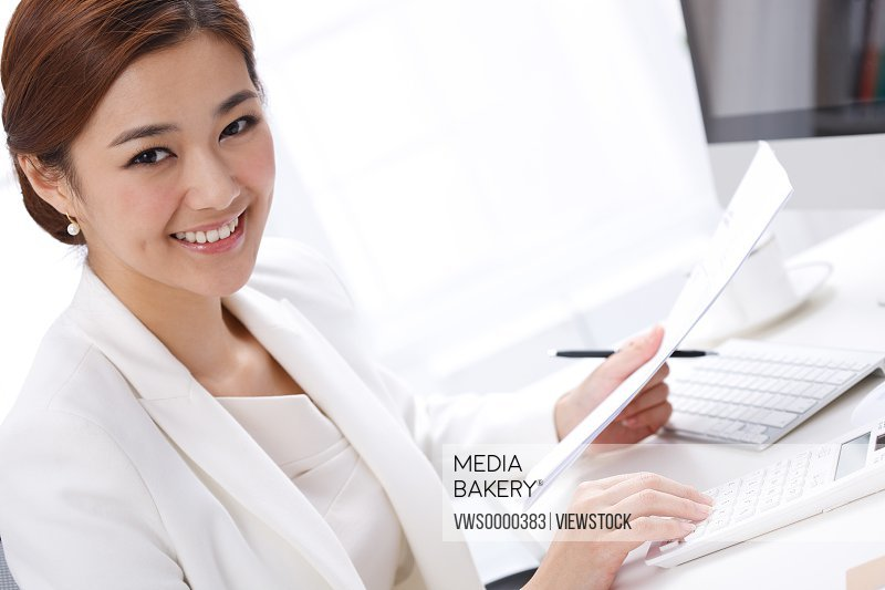 Young business lady using calculator