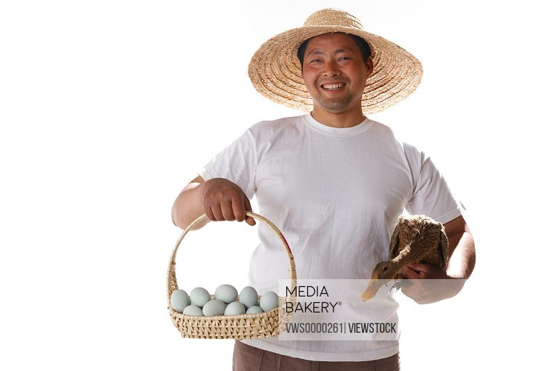 Farmer holding duck's eggs and duck