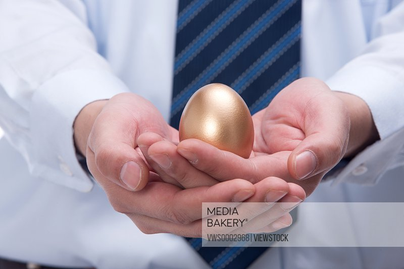 Businessman holding gold egg