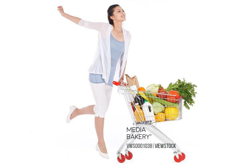 Young woman with vegetables in shopping cart