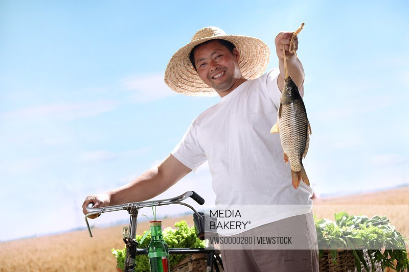 Farmer walking bike with fish and vegetable