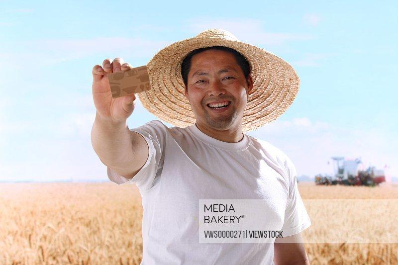 Farmer holding credit card in field