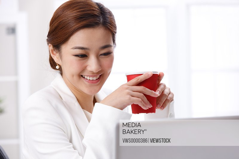 Young business lady drinking coffee