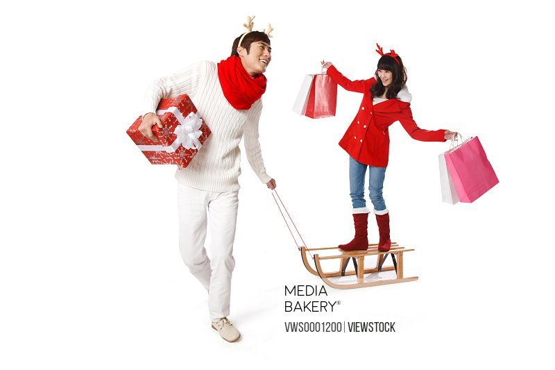 Young man pulling sled and young woman holding bags on it