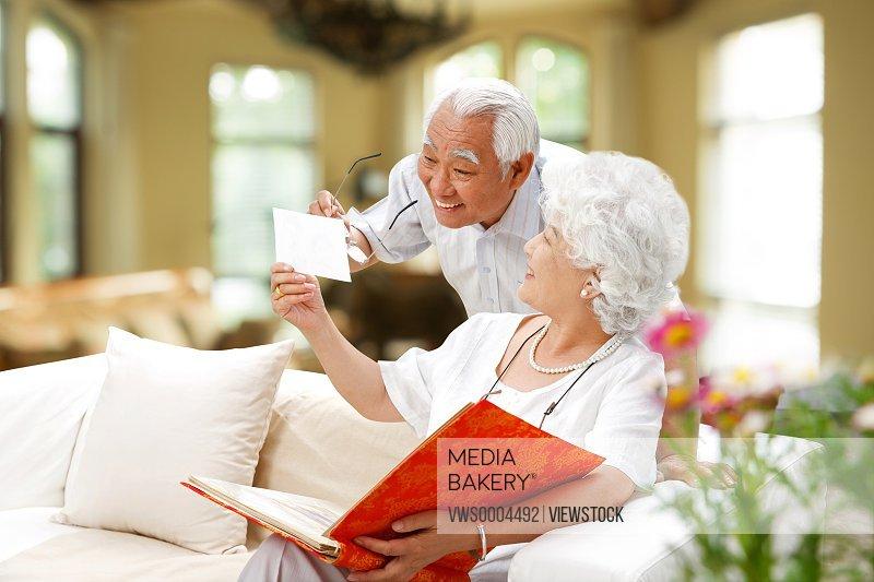Happy Older couple looking album