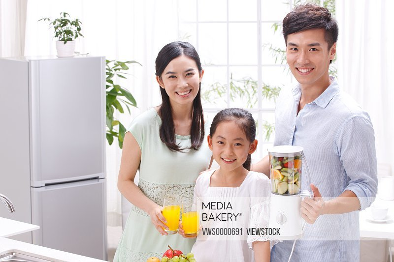 Family holding juice in kitchen