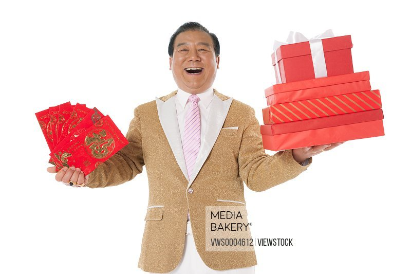 Successful man showing gifts and red lucky envelopes