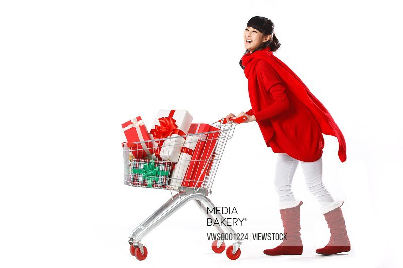 Young woman with Christmas in shopping cart