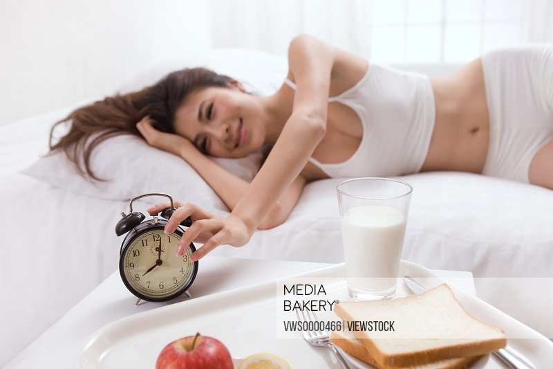 Young lady lying on bed with alarm clock,milk,bread and fruit