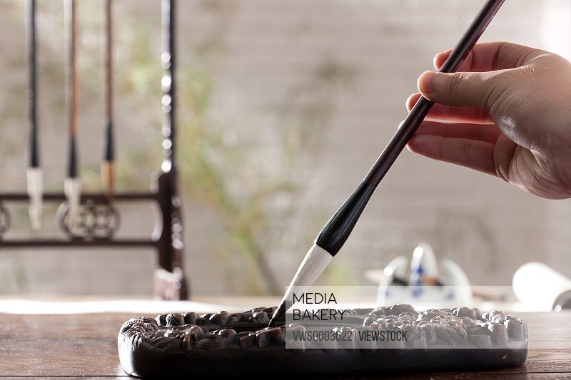 Holding a Chinese writing brush