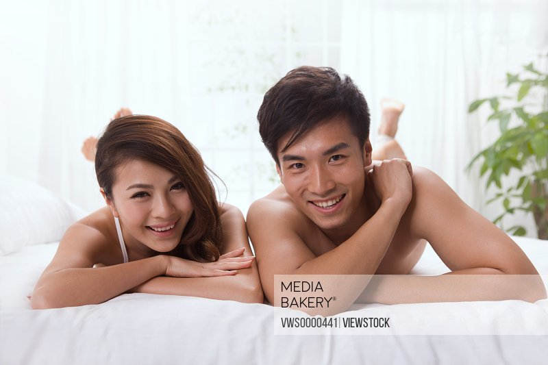 Young couple lying prone on bed